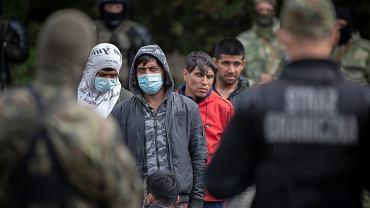 Migranci na polsko-białoruskiej granicy pilnowani przez strażników z obu stron. 19 sierpnia 2021 roku