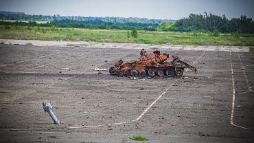 Zniszczony czołg i pocisk artyleryjski wbity w asfalt na byłym lotnisku w pobliżu Doniecka