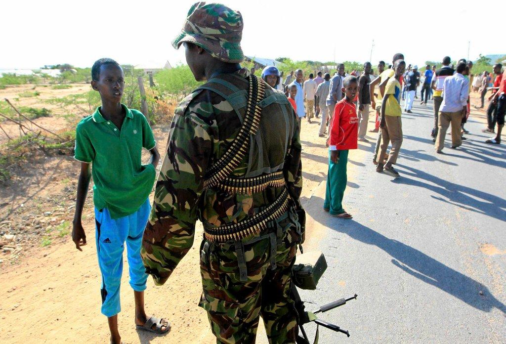 Żołnierz kenijskich sił zbrojnych zatrzymuje chłopca idącego w kierunku kampusu