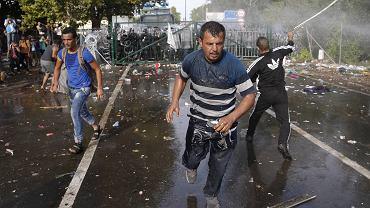 """WRZESIEŃ. 16 września węgierska policja użyła w przeciw imigrantom na granicy gazu łzawiącego i armatek wodnych. Przedtem Węgrzy aresztowali ponad pół tysiąca osób, które przedarły się z Serbii. Do starć doszło na granicy między miejscowościami Horgos w Serbii i Röszke na Węgrzech. Tysiące imigrantów, w tym wielu uchodźców z Syrii, Iraku i Afganistanu, zmierzały tędy do Austrii i Niemiec, dopóki Węgrzy nie zamknęli przejścia. Uciekinierzy zaczęli protestować za płotem, Według węgierskiej policji byli agresywni. Ujęcia telewizyjne pokazały, że imigranci rzucali w policjantów butelkami z wodą i innymi przedmiotami. Krzyczeli: """"Otwórzcie bramę!""""."""