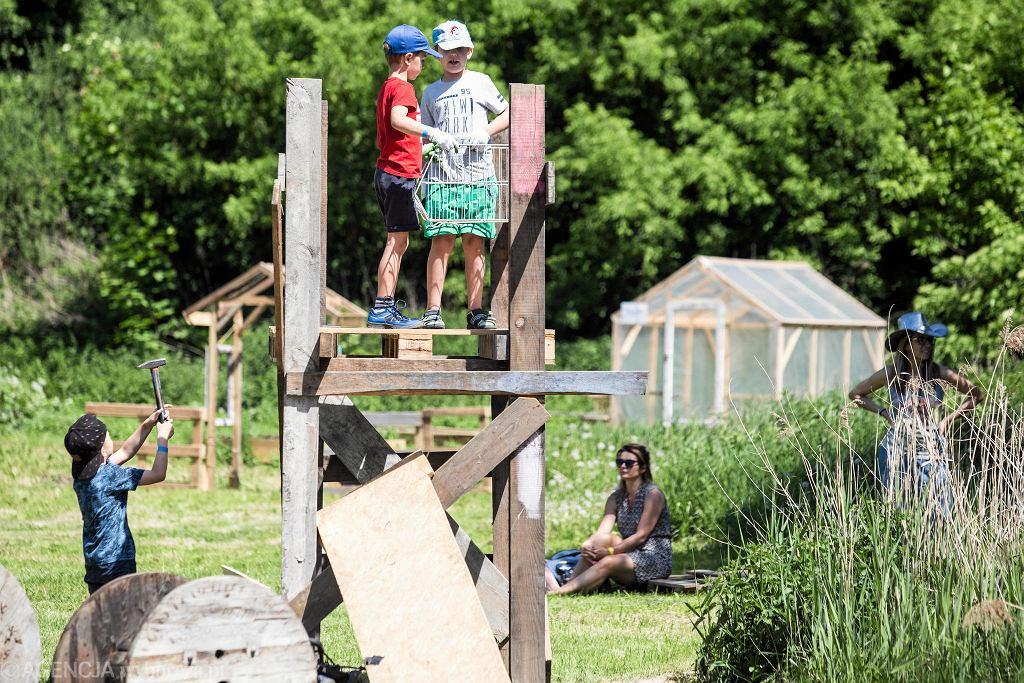 Pierwszy w Polsce przygodowy plac zabaw znów jest otwarty. W ubiegłym roku działał jedynie przez trzy tygodnie sierpnia. Tym razem czynny będzie niemal do końca października. Sobota była dniem rodzinnym w Rezerwacie Dzikich Dzieci, co oznacza, że dziecko mogło wejść na teren placu z rodzicem. Zwykle nie jest to możliwe, bo Rezerwat powstał po to, by chronić dziecko do nieskrępowanej zabawy, tak by nie słyszało ciągłych zakazów: nie rób tego, nie rób tamtego. Rezerwat Dzikich Dzieci składa się z dwóch części. W kuchni błotnej mogą bawić się wszyscy bez względu na wiek ( i w towarzystwie rodziców). Do właściwej części placu mogą wchodzić jedynie dzieci, które ukończyły siedem lat. Tutaj z pomocą desek i prawdziwych narzędzi budują tu dowolne konstrukcje. Rezerwat znajduje się przy ul. Dolnej Panny Marii, na terenie parafii Nawrócenia św. Pawła. Finansowany jest z budżetu obywatelskiego.