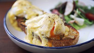 Jajka po benedyktyńsku to inaczej jajka w koszulkach z dodatkiem sosu holenderskiego, podane na grzankach