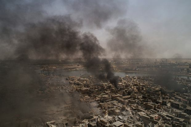 Smoke billows over the Old City after several strikes as Iraqi forces continue their advance against Islamic State militants in Mosul, Iraq, Monday, July 3, 2017. (AP Photo/Felipe Dana)