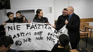 Spotkanie o żołnierzach wyklętych, prowadzone przez Młodzież Wszechpolską w X LO w Toruniu. Dyrektor Michał Dąbkowski odbiera transparent przeciwnikom spotkania