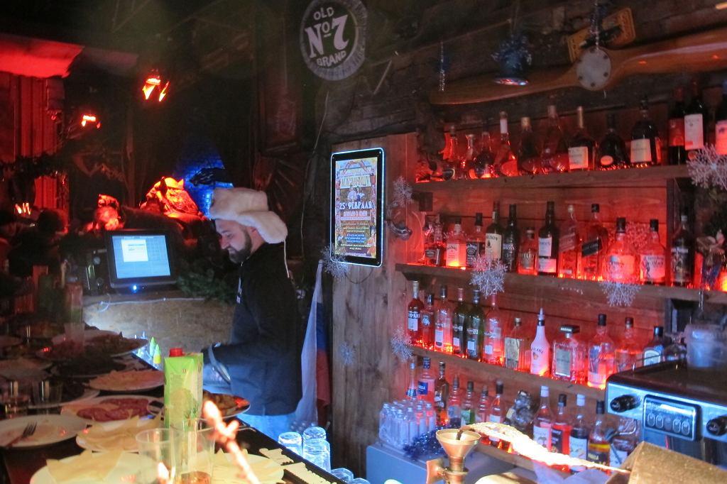 Klubowy bar jest dobrze zaopatrzony. Mrozu w pomieszczeniach nie ma, ale czapka uszatka zawsze dodaje barmanowi fasonu (fot. Lech Potyński)
