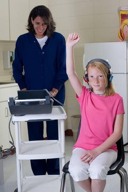 Osoba badana siedzi w wyciszonej kabinie, w słuchawkach na uszach, przez które słyszy różnorodne tony czyste, od głębokich, niskich basów po wysokie, cienkie piski