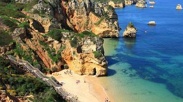 Portugalia Algarve. 1) Algarve pogoda: lato w tej portugalskiej prowincji trwa od czerwca do września. Średnie najwyższe temperatury zaczynają się od 20oC, by wzrosnąć aż do 28oC w lipcu i sierpniu, natomiast we wrześniu kształtują się one w granicach 26oC. Aby uniknąć upałów warto wybrać się do Algarve w czerwcu lub wrześniu. Jesienią (październik, listopad) średnie temperatury powietrza oscylują w granicach 22oC w październiku i 19oC w listopadzie. Wtedy też zdarzają się opady, jednak ich poziom nie przekracza 50mm/m2 - wiążą się one przeważnie ze sztormami, które nawiedzają Algarve kilka razy w ciągu jesieni. Średnie najwyższe temperatury wiosną wynoszą od 18oC w marcu, przez 20oC w kwietniu, aż do 22oC w maju. 2) Algarve woda: morze w okolicach Algarve najcieplejsze jest od sierpnia do października - 22oC. Od maja do lipca temperatura wody rośnie od 17 do 20oC. 3) Algarve plaże: południowe wybrzeże Portugalii słynie z piaszczystych plaż wciśniętych między skały i urwiska. Wiele z nich, mieszczących się w niewielkich zatoczkach, poprzecinanych jest niesamowitymi formami skalnymi. Popularne plaże to: Praia do Amado Beach - świetne miejsce do uprawiania surfingu, czy też Quarteira Beach - ze względu na bliskość deptaka i łatwy dojazd często wybierana przez rodziny z dziećmi. 4) Algarve atrakcje: Przylądek świętego Wincentego - najdalej na południe wysunięty fragment Portugalii i całej Europy, określany jako koniec świata; Milreu - miasteczko przyciągające przede wszystkim turystów zainteresowanych antycznymi zabytkami; Faro - najpopularniejsze miasto w całym regionie, z ciekawą starówką otoczoną murami obronnymi i Se - katedrą, która na skutek wielu przebudów łączy w sobie kilka stylów architektonicznych; oraz Muzeum Morskim i Kaplicą Kości (atrakcja dla turystów o mocnych nerwach), która mieści ponad 1000 kości mnichów; Parque Natural da Ria Farmosa - laguna będąca siedliskiem wielu gatunków ptactwa wodnego i skorupiaków;  Silves - malownicze miasto o długiej hist