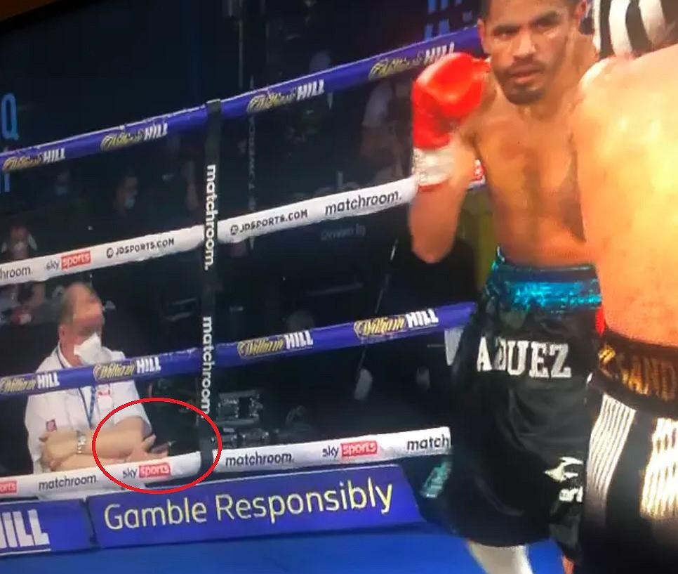 Sędzia bokserski patrzył na telefon, zamiast na ring