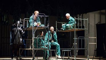 Ateny to więzienie, na scenie widzimy kraty, prycze i zielone drelichy