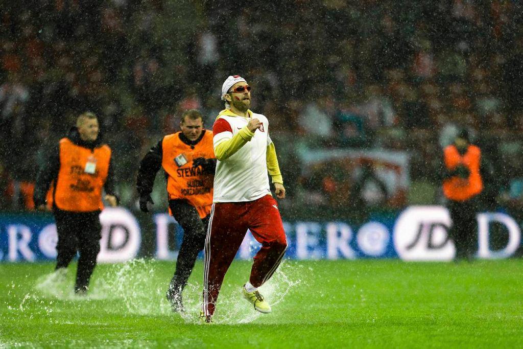 Kibic, który wbiegł na zalaną murawę Stadionu Narodowego, ucieka przed stewardami