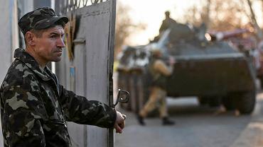 Ukraiński żołnierz otwiera bramę bazy Nowofiedorowko na Krymie. Przez bramę wjeżdża transporter opancerzony (pro)rosyjskich wojsk. Baza była jedną z ostatnich ukraińskich instalacji wojskowych na Krymie w rękach Kijowa. 24.02.2014 r. Ukraina zdecydowała o wycofaniu wojsk z Krymu