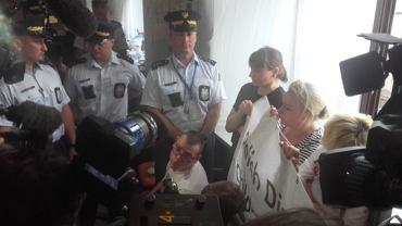 Protestujący z banerem, który miał zawisnąć na oknie sejmu