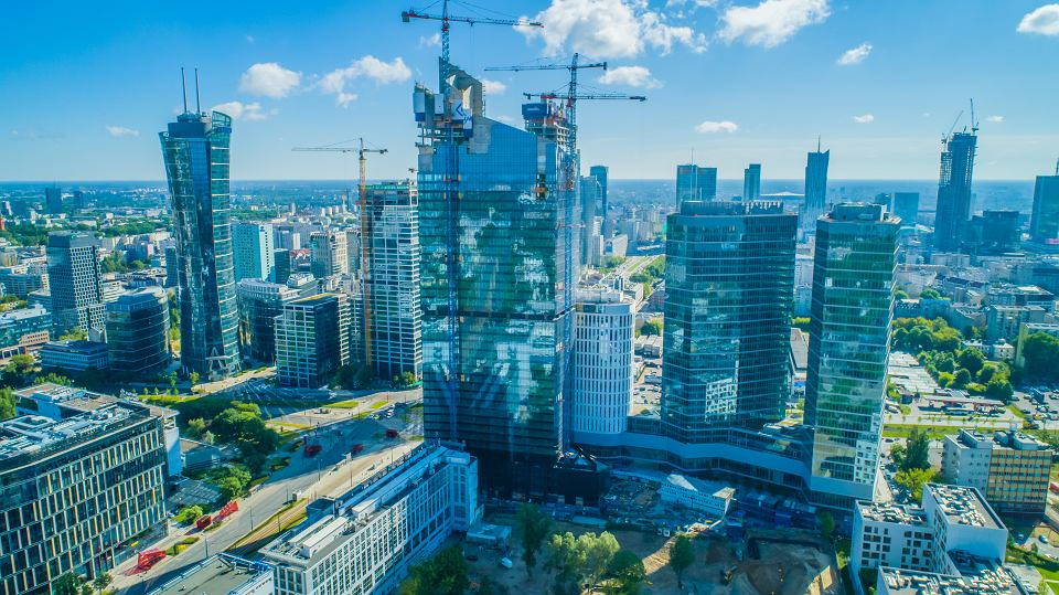 W centrum zdjęcia 195-metrowy wieżowiec Skyliner. Na lewo od niego budowa wieżowca Generation Park (140 m), ponad nim  - szczyt powstającego wieżowca Warsaw Unit (202 m). Na prawo - 86-metrowy hotel i dwa 130-metrowe biurowce The Warsaw Hub. W tle, przy prawym brzegu - budowany 310-metrowy Varso Tower