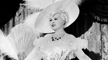 Mae West, popularna w latach 30. aktorka uznawana za symbol prowokacyjnej i wyzwolonej kobiecości, wylansowała modę na szykowne suknie wężowe i strusie pióra.