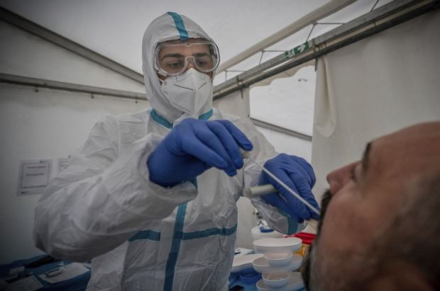 Medical personnel perform a Covid-19 PCR smear on a man at a corona test center in Berlin, Germany, Wednesday, Oct. 14, 2020. (Michael Kappeler/dpa via AP)