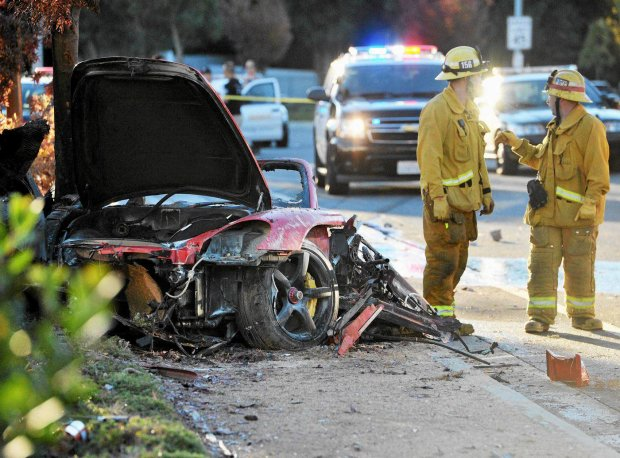 ADDS MANDATORY CREDIT- First responders gather evidence near the wreckage of a Porsche sports car that crashed into a light pole on Hercules Street near Kelly Johnson Parkway in Valencia on Saturday, Nov. 30, 2013. A publicist for actor Paul Walker says the star of the