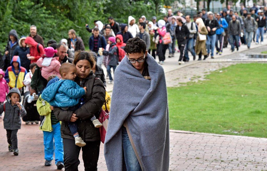 Emigranci z Afryki idą z dworca w Dortmundzie do obozu dla uchodźców.