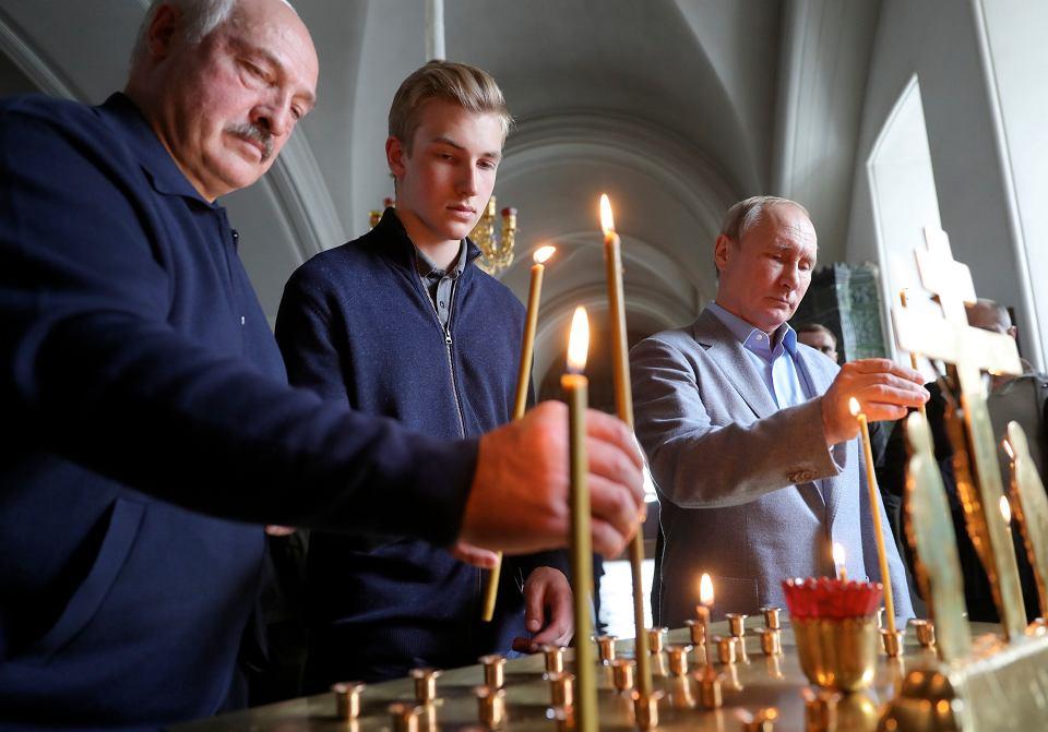 Aleksander Łukaszenka z synem Kolią i Władimir Putin zapalają świece w Monastyrze Wałamskim w rosyjskiej Karelii, 17 lipca 2019 r.
