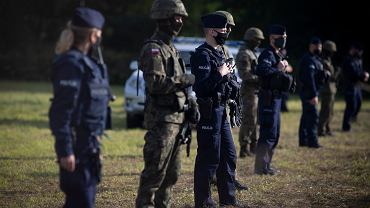 Straż graniczna, ludzie w wojskowych mundurach (pozbawionych oznaczeń identyfikujących formację) i policja od kilkunastu dni przetrzymują pod gołym niebem grupę migrantów. Nie przyjmują od nich wniosków o azyl, nie dopuszczają do nich pomocy, ich pełnomocników i dziennikarzy. Białorusini ni pozwalają im się cofnąć. Usnarz Górny, 25 sierpnia 2021