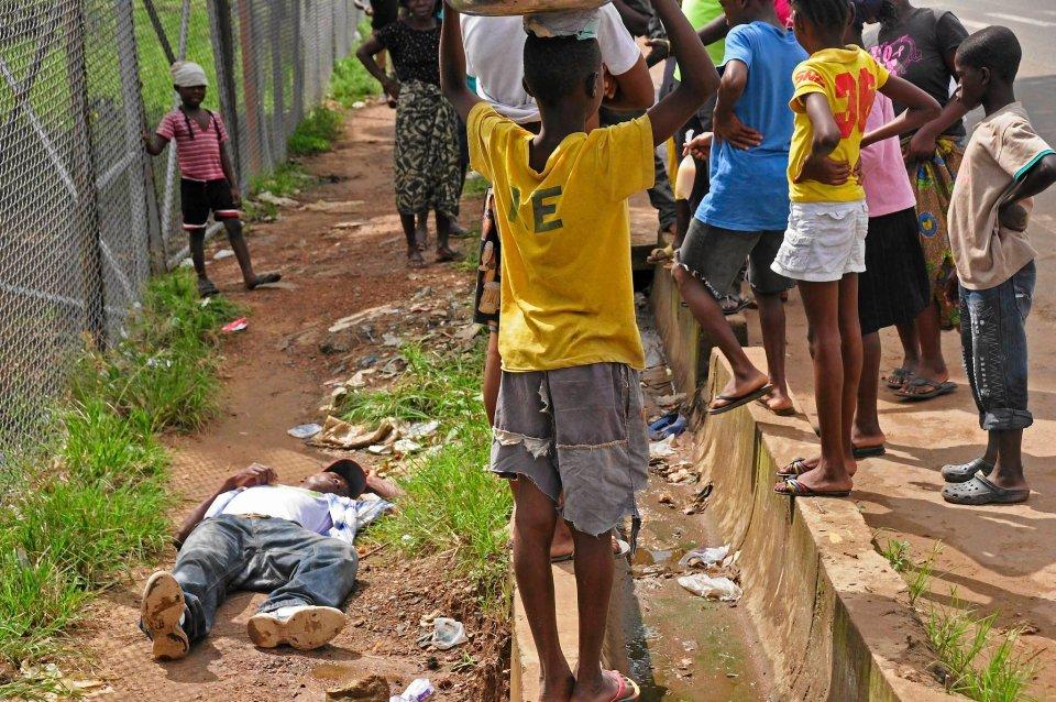 Dzieci otaczające mężczyznę, który upadł na ulicy Monrowii (Liberia). Najprawdopodobniej jest kolejną ofiarą wirusa.