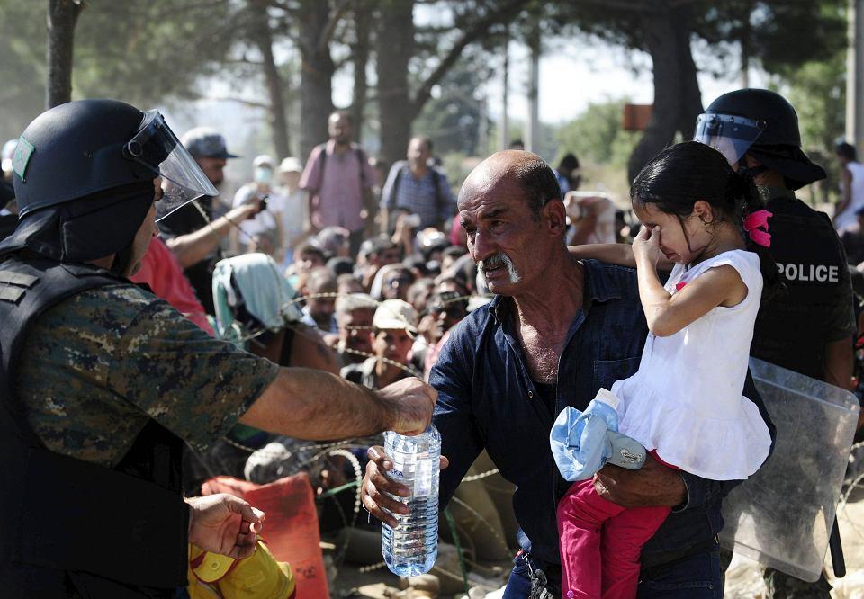 Policjant podaje wodę imigrantom, którzy próbują się dostać do Macedonii. Na granicy Grecji z Macedonią dochodzi do dantejskich scen. Przez oba kraje prowadzi główny szlak uchodźców i imigrantów zmierzających do Unii Europejskiej