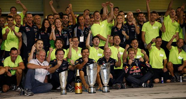 Red Bull Formula One driver Sebastian Vettel of Germany (front R) and Red Bull Formula One driver Mark Webber of Australia (C) celebrate with the Red Bull team after the Abu Dhabi F1 Grand Prix at the Yas Marina circuit on Yas Island, November 3, 2013. Sat next to them is Red Bull technical chief Adrian Newey (front, 2nd R) and team principal Christian Horner (front, center L).        REUTERS/Steve Crisp (UNITED ARAB EMIRATES  - Tags: SPORT MOTORSPORT SPORT MOTORSPORT F1)