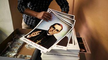 Wolontariusz trzymający plakaty z wizerunkiem Oscara Romero