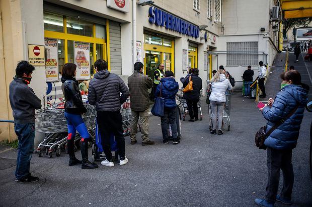 Ludzie ustawiają się w kolejce do supermarketu w Rzymie, zachowując 'bezpieczną' odległość  w obawie przed rozprzestrzenianiem się koronawirusa.