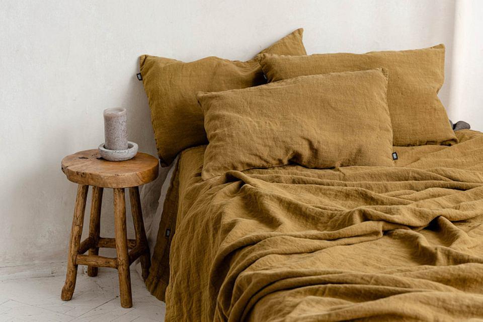 Lniana narzuta i poduchy Golden Ochre to stylowa prostota, która przyjemnie chłodzi latem, a zimą otula.