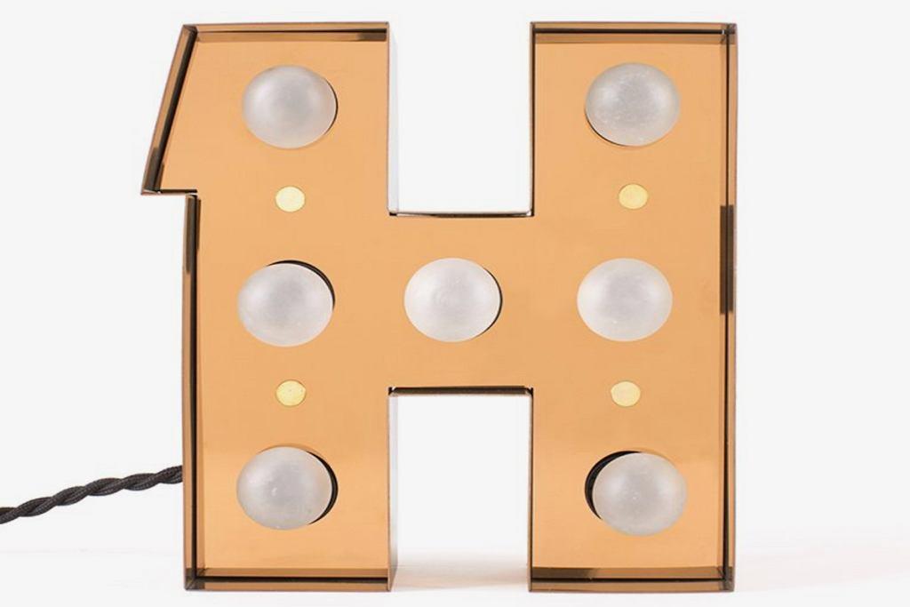 Złota lampa ścienna w kształcie litery H.