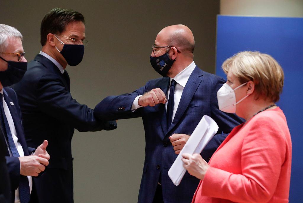 Jest porozumienie na szczycie UE. Na zdjęciu: Premier Holandii Mark Rutte i przewodniczący Rady Europejskiej Charles Michel przybijają sobie 'piątkę' łokciami. Przed nimi kanclerz Niemiec Angela Merkel