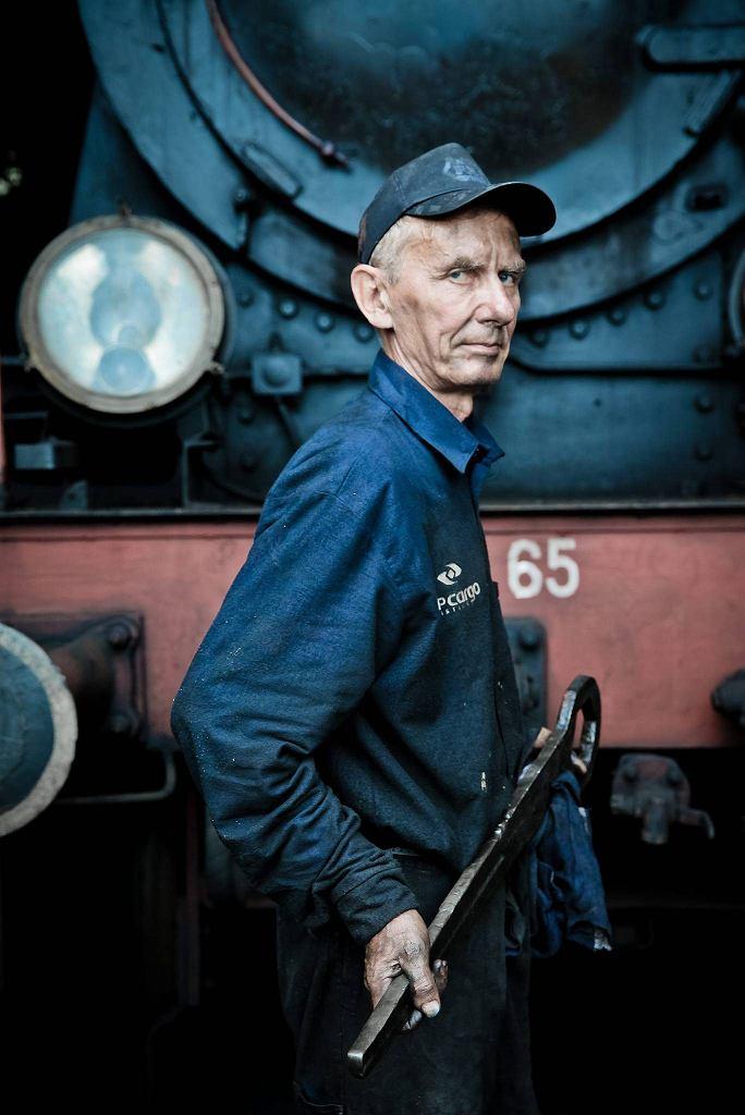 Edward Szmydt, na kolei od 27 lat, monter specjalista w Wolsztynie. Reperuje parowozy ? takie, w których trzeba rozpalić w piecu, żeby pojechały w trasę. Wyjeżdżają z parowozowni dwa razy na dzień, od poniedziałku do piątku. Wjeżdżają na Dworzec Główny w Poznaniu i ludzie się dziwią, że kolejarze jeszcze w piecu palą. Najważniejsze podróże Szmydt w życiu miał, kiedy pracował na kolei w Tychach. Raz w miesiącu, w sobotę, wsiadał w Katowicach do pociągu relacji Przemyśl ? Szczecin, po 13 godzinach wysiadał w Gryfinie, potem jeszcze trochę kilometrów autobusem i kawałek polami na nogach. Dla dziewczyny miał popołudnie, wieczór, poranek. Rok tak podróżował. Potem wzięli ślub, urodziły się dwie córki. Najdalej był z kolejarzami w Budapeszcie; parowozem pojechali, na zaproszenie muzeum, ale jego nazwy nie pamięta. Jechali na zimno, to znaczy elektryk ciągnął parowóz i wagon socjalny. Po Węgrzech pojeździli na ciepło, do Polski wracali na zimno.