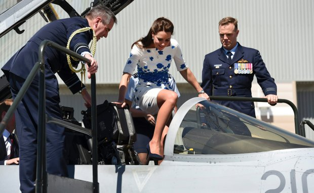 Britain's Kate, the Duchess of Cambridge, flanked by Chief of Air Force Air Marshall Geoff Brown, left, and Commanding Officer of Number 1 Squadron, Wing Commander Stephen Chappell, makes her way into the cockpit of a RAAF Super Hornet from 1 Squadron at RAAF Base Amberley, near Brisbane, Australia, Saturday, April 19, 2014. The Duke and Duchess of Cambridge are on a three-week tour of Australia and New Zealand, the first official trip overseas with their son, Prince George. (AP Photo/William West, Pool)