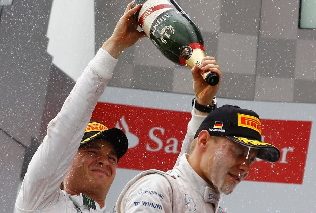 Mercedes Formula One driver Nico Rosberg of Germany (L) pours champagne on Williams driver Valtteri Bottas of Finland, as he celebrates on the podium after winning the German F1 Grand Prix at the Hockenheim racing circuit July 20, 2014. Rosberg won his home German Grand Prix for Mercedes on Sunday to stretch his overall lead in the Formula One championship to 14 points.Lewis Hamilton, his team mate and only real title rival, finished third after starting in 20th place. Bottas took second place for Williams. Rosberg's win was the first for a works Mercedes team in Germany since Argentine Juan Manuel Fangio in 1954 and his fourth victory of the season.                          REUTERS/Ralph Orlowski  (GERMANY  - Tags: SPORT MOTORSPORT F1)