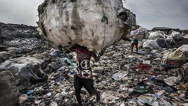 Lagos. Mężczyzna wynosi wór plastikowych butelek z wysypiska Olusosun