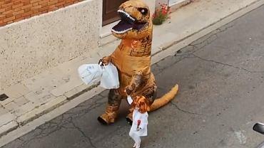 Tata w stroju dinozaura i jego córka przebrana za bohaterkę z filmu wyrzucają śmieci.