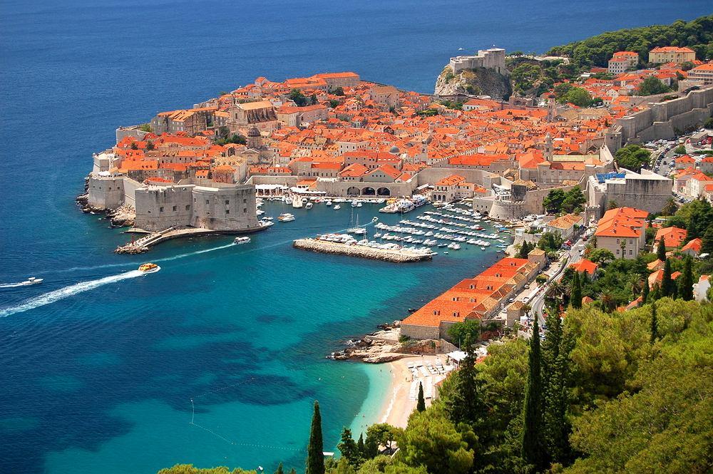 Dalmacja, Dubrownik, Chorwacja. Obszar Dalmacji rozciąga się wzdłuż wybrzeża Adriatyku od wyspy Pag do Zatoki Kotorskiej. To tu znajdują się najładniejsze chorwackie miasta, fantastyczna przyroda, a także tysiąc wysp i wysepek. Perła Dalmacji to bez wątpienia Dubrownik. Inne piękne miasto Dalmacji to Split. Z wysp trzeba odwiedzić Hvar. Do atrakcji przyrodniczych Dalmacji należy Park Narodowy Krka.