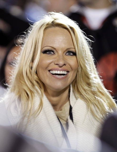 Actress Pamela Anderson watches the NCAA Carrier Classic men's college basketball game between Michigan State Spartans and the North Carolina Tar Heels on the deck of the aircraft carrier USS Carl Vinson in Coronado, California November 11, 2011.   REUTERS/Mike Blake     (UNITED STATES - Tags: SPORT BASKETBALL MILITARY ENTERTAINMENT HEADSHOT)
