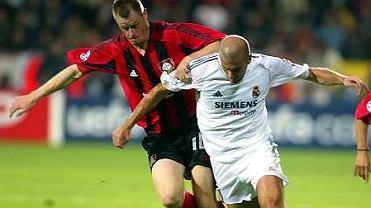 Jacek Krzynówek walczy o piłkę z Zinedine'em Zidane'em.