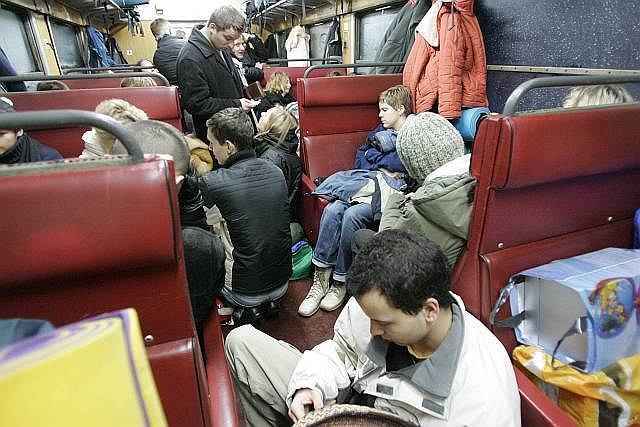 Ludzie siedzą na ziemi, a torby zajmują miejsca. Ciekawe, czy bagaże mają bilety?