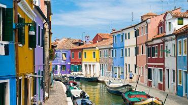 """Większość turystów przybywających do Wenecji nie wie, że w pobliżu słynnego miasta na wodzie, jest jeszcze wiele innych ciekawych i wartych uwagi miejsc. Zaledwie 9 kilometrów od Wenecji znajduje się niewielka rybacka wysepka Burano. To niezwykle przyjemne, mieniące się kolorami miejsce zwane """"perełką weneckiej laguny""""."""
