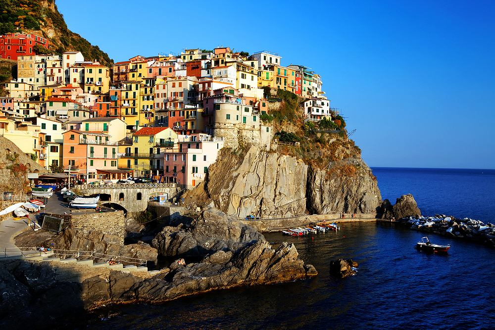Liguria, Włochy. W północno-zachodniej części Włoch, nad brzegiem Morza Śródziemnego, leży prowincja Liguria. Jest tu wiele uroczych miasteczek i wiosek, ale wizytówką Ligurii jest pięć wyjątkowych miasteczek - Cinque Terre (Pięć Ziem): Manarola, Monterosso al Mare, Corniglia, Vernazza i Romaggiore - wszystkie bardzo kolorowe i rozłożone malowniczo na skalistym morskim brzegu.