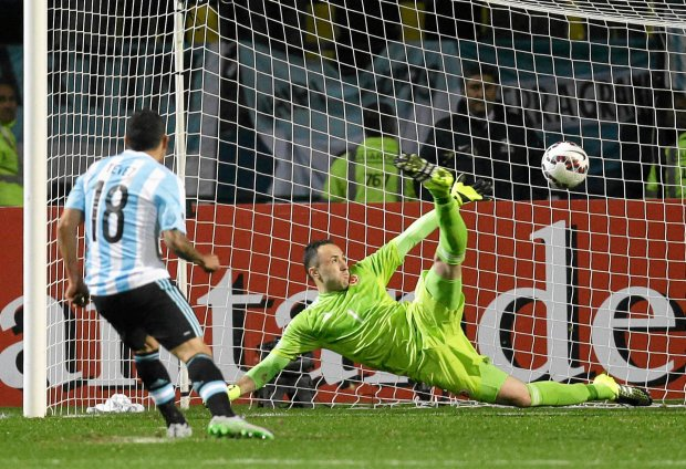 Argentina's Carlos Tevez, left, scores the winning goal past Colombia goalkeeper David Ospina during a penalty shoot out at the end of a Copa America quarterfinal soccer match against Colombia at the Sausalito Stadium in Vina del Mar, Chile, Friday, June 26, 2015. Argentina defeated Colombia 5-4 on penalties after a 0-0 draw on Friday to reach the semifinals of the Copa America. (AP Photo/Natacha Pisarenko) SLOWA KLUCZOWE: XXCopaAmerica2015XX