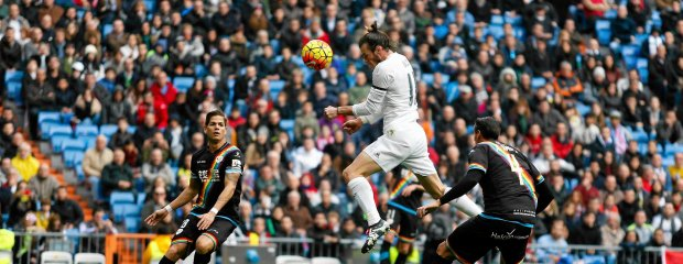 Real Madrid's Gareth Bale heads the ball to score past Rayo Vallecano's Antonio Amaya, right, and Ze Castro, left, during the Spanish La Liga soccer match between Real Madrid and Rayo Vallecano at the Santiago Bernabeu stadium in Madrid, Sunday, Dec. 20, 2015. (AP Photo/Francisco Seco) SLOWA KLUCZOWE: XLALIGAX