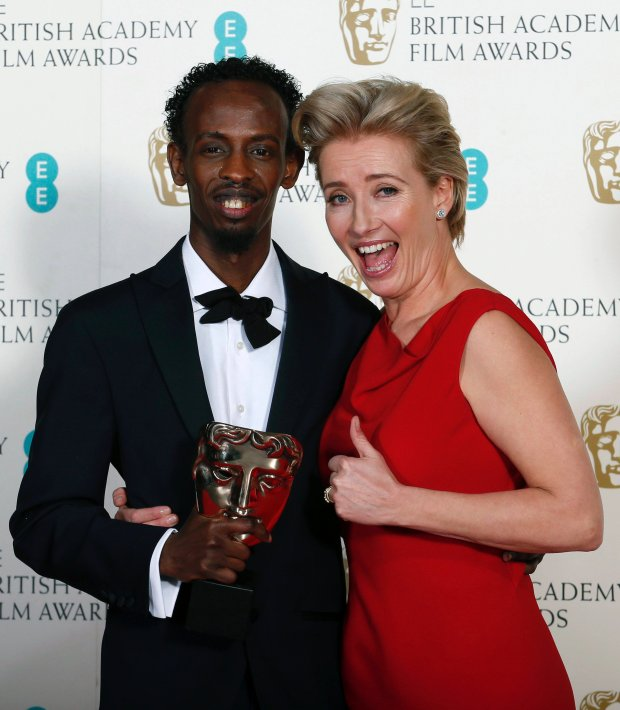 "Barkhad Abdi (L) celebrates winning Best Supporting Actor for ""Captain Phillips"" with Emma Thompson at the British Academy of Film and Arts (BAFTA) awards ceremony at the Royal Opera House in London February 16, 2014. REUTERS/Suzanne Plunkett (BRITAIN - Tags: ENTERTAINMENT)"