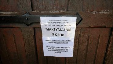 Ogłoszenie dotyczące obostrzeń na drzwiach kościoła Świętego Krzyża w Kielcach