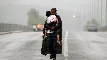 Syryjski uchodźca całuje swoją córkę, idąc w ulewnym deszczu w kierunku granicy Grecji z Macedonią, w okolicy greckiej wioski Idomeni, 10 września 2015 roku. Jak podała  Organizacja Narodów Zjednoczonych, większość z ludzi docierających do Europy to uchodźcy uciekający przed przemocą i prześladowaniem w swoich krajach macierzystych.
