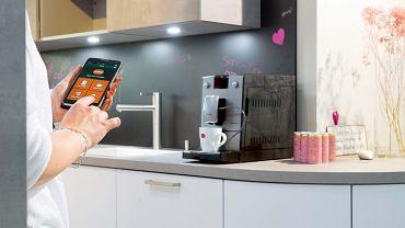 Ekspres do kawy CAFEROMATICA 768 możesz włączyć zdalnie przy użyciu smartfona, nie ruszając się złóżka. Zaparzy twój ulubiony napój według przepisu, który zapisałeś wpamięci ekspresu, około 3199 zł, Nivona