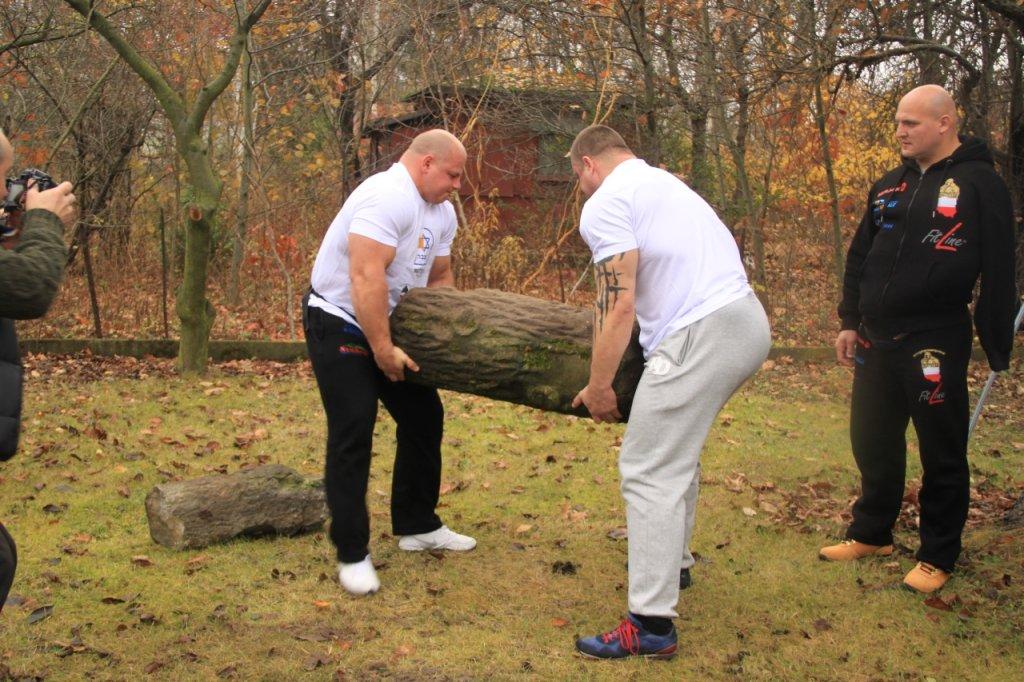 Strongmani - Tomasz Kowal oraz Grzegorz Wiśniewski - pomagają przenieść cięższą z macew, której waga przekracza 250 kg