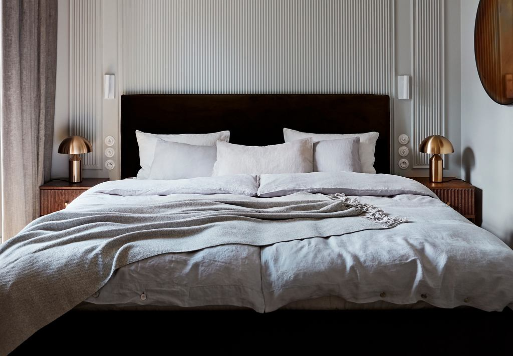 Sypialnia ozdobiona kołdrą, poduszkami i narzutą z alpaki.